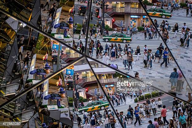 People are seen reflected in a shopping mall mirror at a busy intersection in the shopping district of Harajuku on June 18 2015 in Tokyo Japan