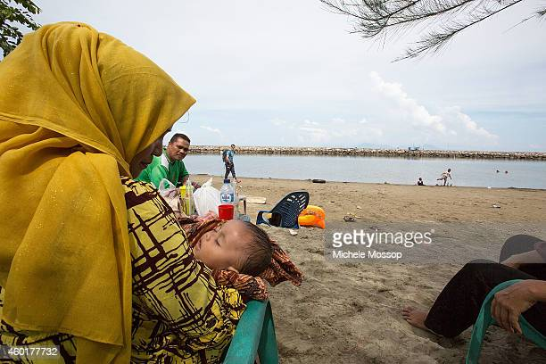 People are seen relaxing on the beach on December 5 2014 in Banda Aceh Indonesia The Indoensian province of Aceh was the worst hit location with...