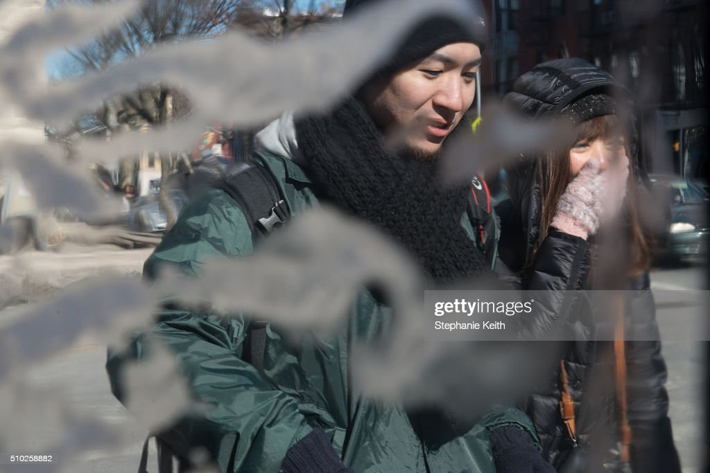 People are seen through frosted over plastic sheeting during an arctic chill that brought frigid temperatures on February 14, 2016 in the Brooklyn borough of New York City. The city broke a 100-year record February 14, as emputures dropped minus 1 degree Fahrenheit.