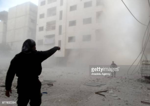People are seen through the dust cloud after Assad regime's warcrafts carried out airstrikes over the deescalation zone of Ein Tarma suburb of the...
