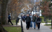 People are seen walking along the campus of Penn State University following a night of rioting at the school in response to the firing of head...
