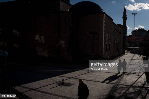 People are seen walking in front of a mosque in the main square on April 11 2017 in Sivas Turkey Campaigning by both the 'Evet' and 'Hayir' camps has...