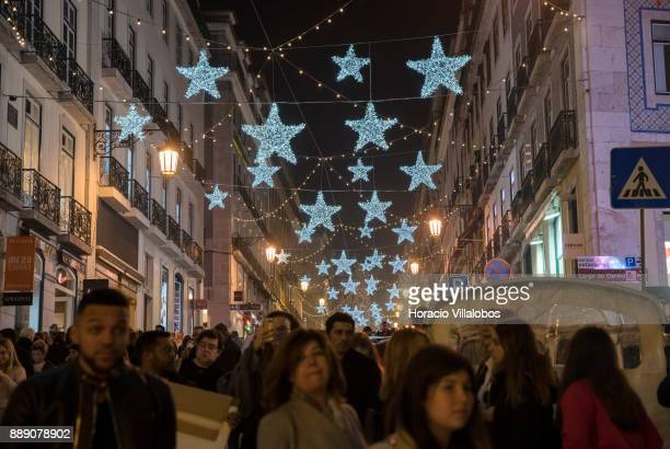 People are seen walking under Christmas and New Year light displays in Rua Garrett on December 9 2017 in Lisbon Portugal The city shows a variety of...