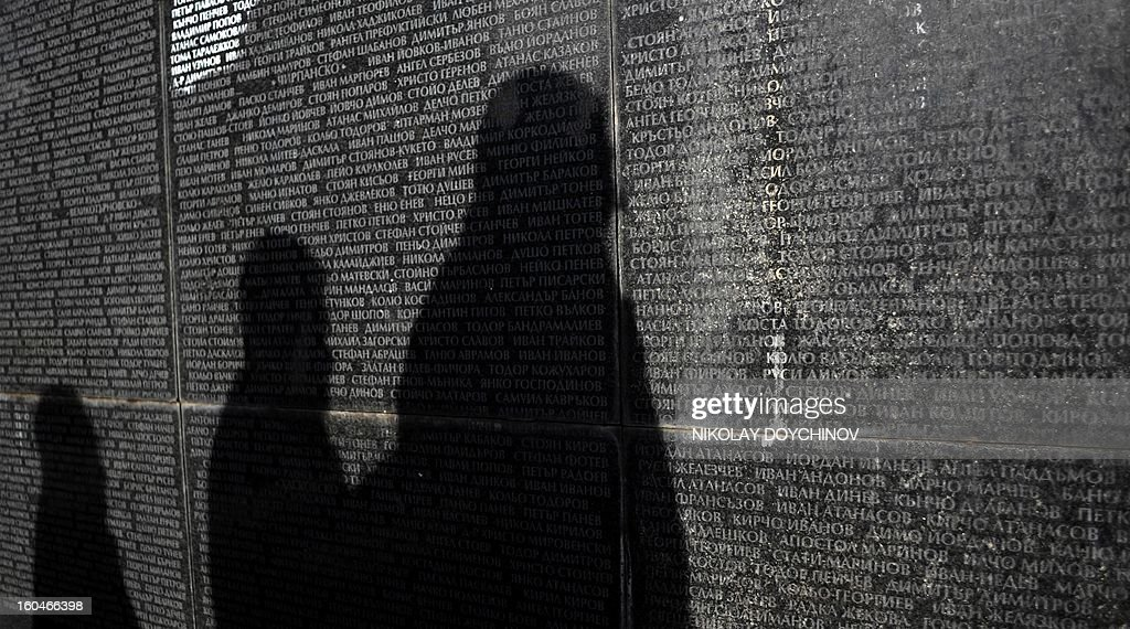People are shadowed on the monument listing the victims of the Communist regime during an open air mass in central Sofia on February 1, 2013. Bulgaria observed of remembrance for the victims of the country's 45-year communist regime at the anniversary of the first killings on February 1, 1945. Between December 1944 and April 1945, the self-proclaimed People's Court set up by the newly established communist regime ordered the killing of 2,730 Bulgarians.