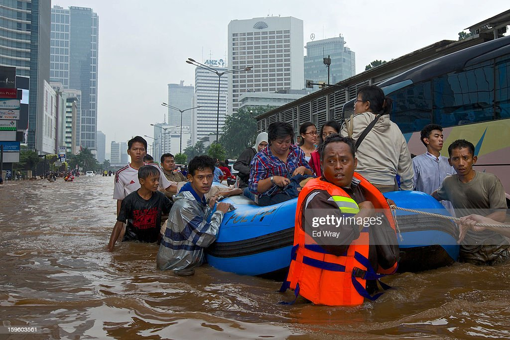 People are stranded by floodwaters in Jakarta's central business district on January 17, 2013 in Jakarta, Indonesia. Thousands of Indonesians were displaced and the capital was covered in many key areas in over a meter of water after days of heavy rain.