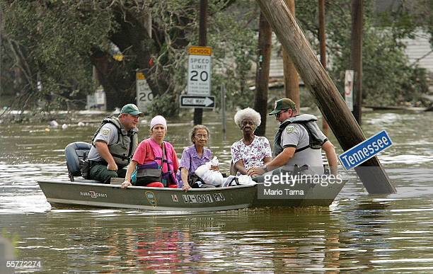 People are taken ashore in a boat after being rescued from their homes in high water in the Ninth Ward after Hurricane Katrina struck August 30 2005...