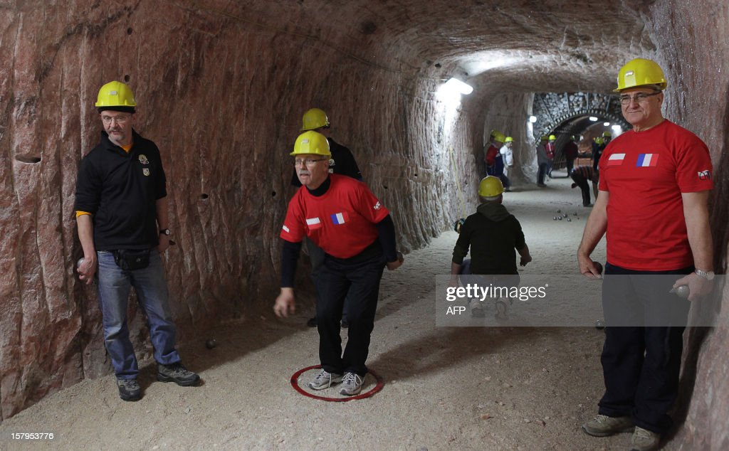 People are taking part in a pétanque tournament in the Klodawa Salt Mine, western Poland on December 7, 2012. The tournament is taking place in a special tourist part of the salt mine located 600 meters under ground.