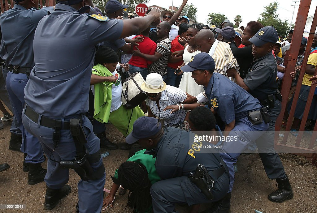 People are trampled after police opened a gate to a park and ride at the Tshwane Events Centre where buses were shuttling wellwishers to a line to view the body of former South African president Nelson Mandela as he lies in state at the Union Buildings on December 13, 2013 in Pretoria, South Africa. Nelson Mandela's body will lie in state for three days as part of a week of events commemorating the life of former South African President. Mr Mandela passed away on the evening of December 5, 2013 at his home in Houghton at the age of 95. Mandela became South Africa's first black president in 1994 after spending 27 years in jail for his activism against apartheid in a racially-divided South Africa.