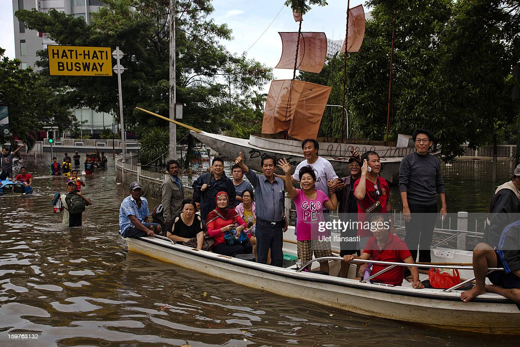 People are transported along a flooded road on a boat as major floods hit North Jakarta on January 20, 2013 in Jakarta, Indonesia. The death toll has risen to at least 21 since severe flooding struck the city on January 17. The US has offrered US$150,000 (Rp 1.44 billion) in aid.