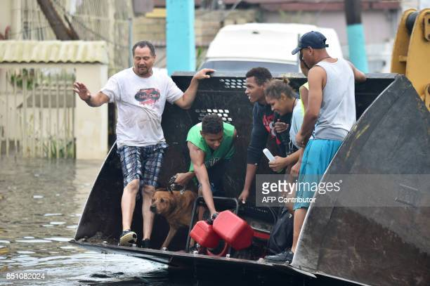 People are transported down a road flooded by Hurricane Maria in Juana Matos Catanon Puerto Rico on September 21 2017 Puerto Rico was facing...