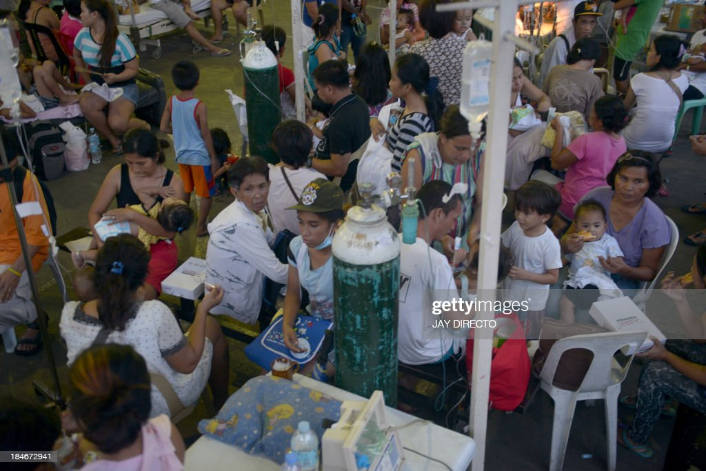 People are treated at a temporary shelter following a 7.1-magnitude quake in Cebu on October 15, 2013. A powerful earthquake killed at least 73 people on October 15 as it tore down modern buildings, destroyed historic churches and triggered terrified stampedes across popular tourist islands in the Philippines. AFP PHOTO / Jay DIRECTO