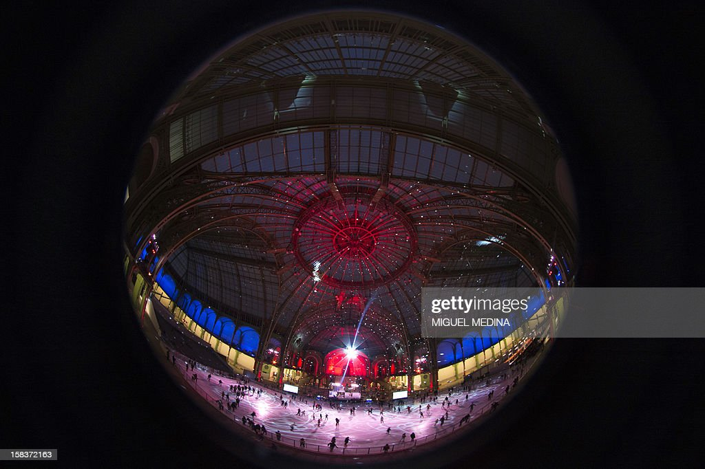 People are viewed in a reflection on a disco ball while skating at dusk on an ice rink hosted in the glass-roofed central hall of the Grand Palais, on December 14, 2012, in Paris. At 1,800 square metres in size, it's the largest rink ever created in France. AFP PHOTO MIGUEL MEDINA