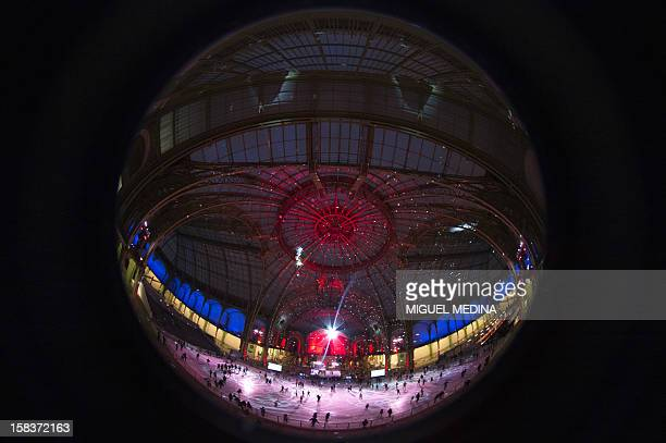 People are viewed in a reflection on a disco ball while skating at dusk on an ice rink hosted in the glassroofed central hall of the Grand Palais on...