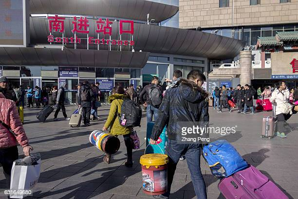 People are walking towards the entrance of Beijing west railway station ready to hurry home by train and spend Spring Festival with their families...