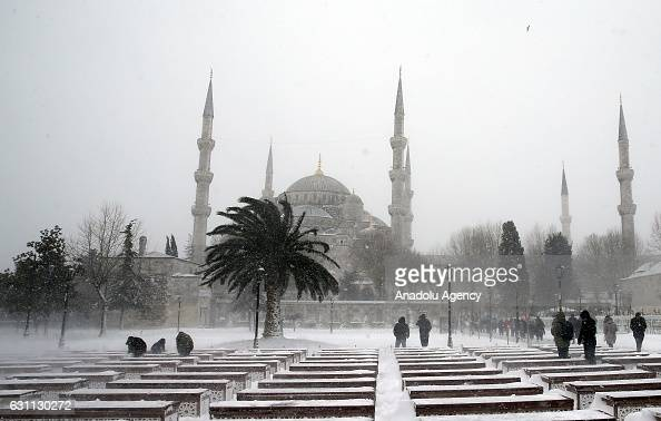 People ares seen at the Sultanahmet Square as the historical Sultanahmet Mosque also known as Blue Mosque is seen at the background during a snowfall...