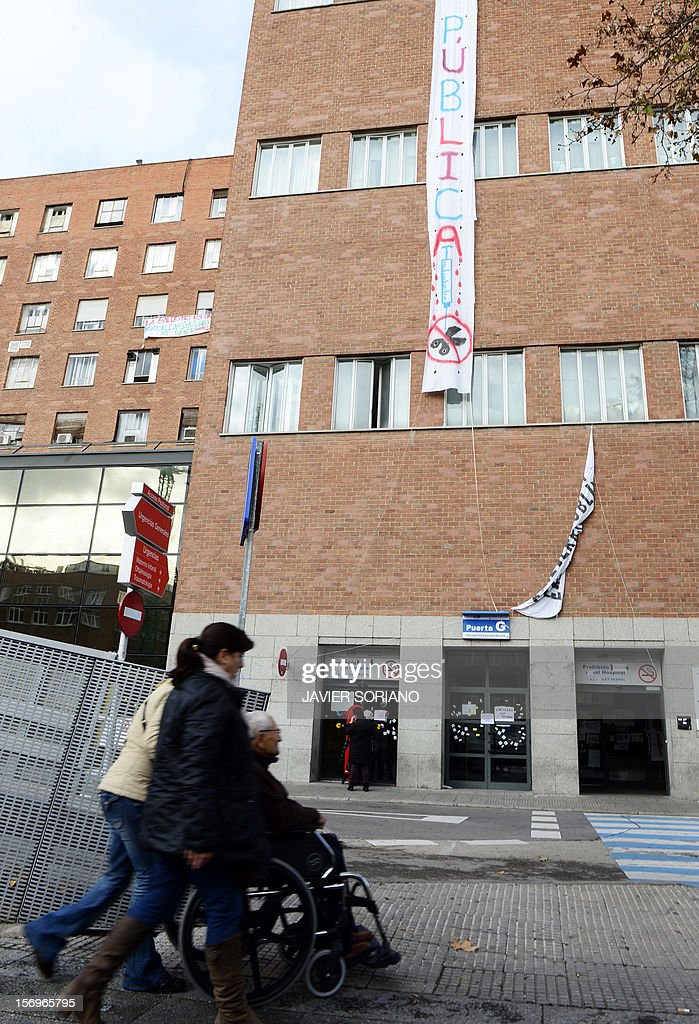 People arrive at the Hospital Clinico San Carlos in Madrid where Spanish doctors, nurses and hospital staff denounce budget cuts and privatisations on November 26, 2012. The health sector has been hard hit by the austerity policies implemented by the rightwing government of Mariano Rajoy, which is trying to cut the public deficit in the eurozone's fourth largest economy. The banner reads: 'health in extinction.'