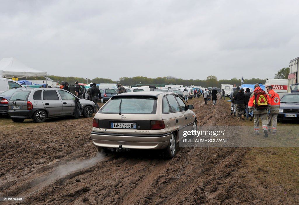 People arrive at the parking to attend the 'Frenchtek 23' Teknival music festival near Salbris, central France on April 30, 2016. / AFP / GUILLAUME