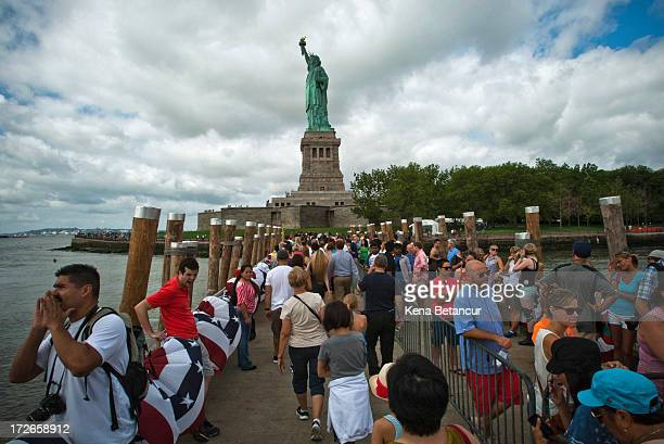 People arrive at the Statue of Liberty on the first day it is open to the public after Hurricane Sandy on July 4 2013 on the Liberty Island in New...