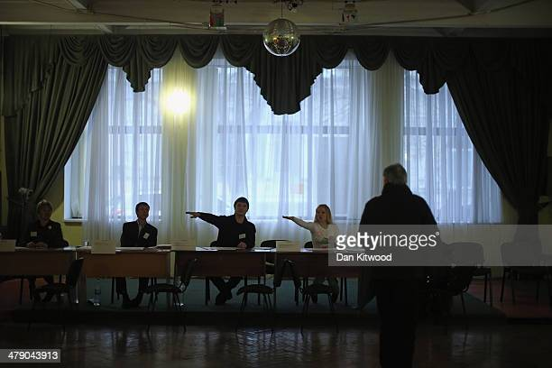 People arrive to cast their vote inside a polling station in Simferopol on March 16 2014 in Simferopol Ukraine Crimeans go to the polls today in a...