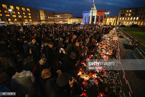 People arrive to lay candles and flowers at the gate of the French Embassy as the Brandenburg Gate stands behind illuminated in the colors of the...