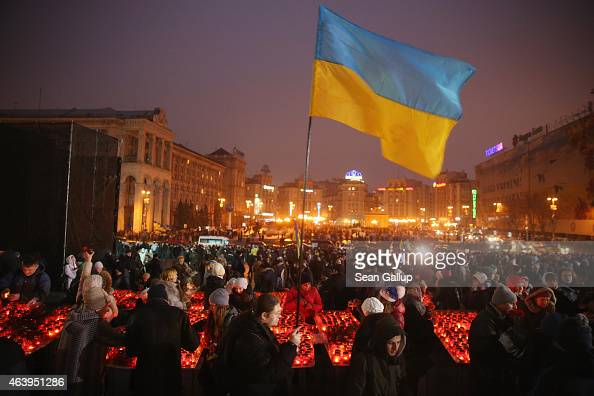 People arrive to lay flowers and light candles in an evening ceremony to commemorate victims of the Maidan uprising one year ago at Maidan square on...