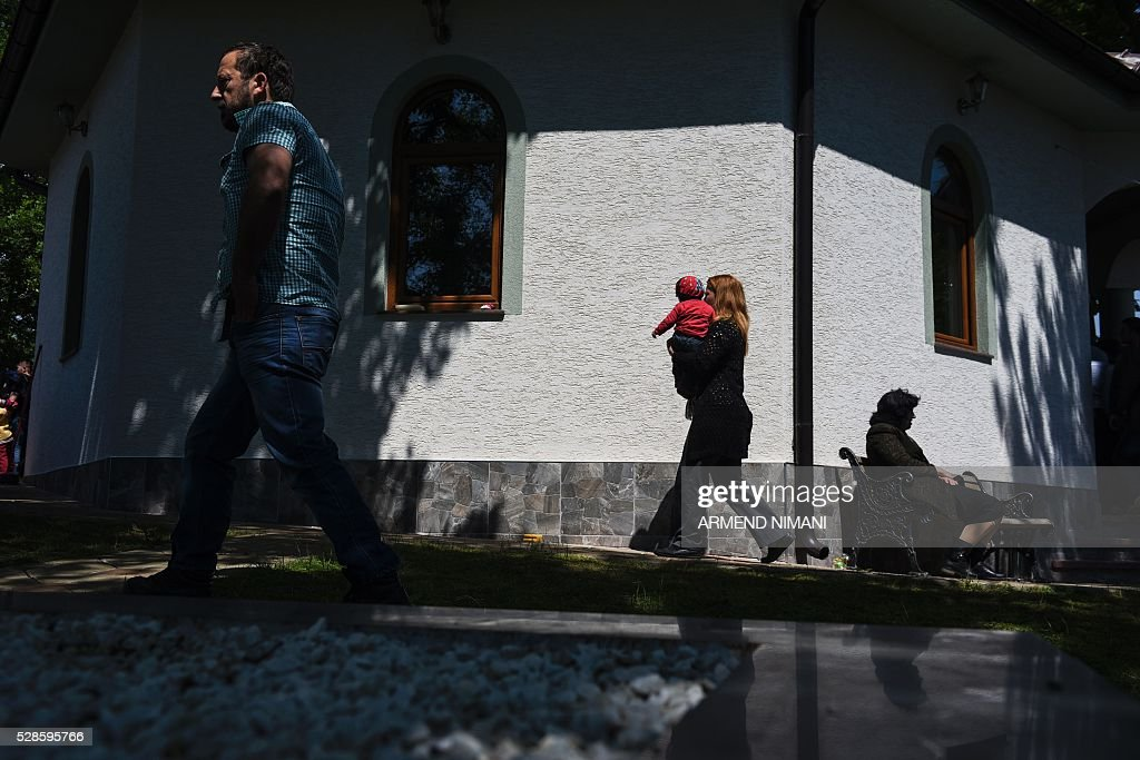 People arrive to the church for praying after sheep were ritually slaughtered in the village of Babaj Bokes on May 6, 2016 during celebrations marking Saint George's Day. Saint George is the patron saint of several countries and cities. / AFP / ARMEND