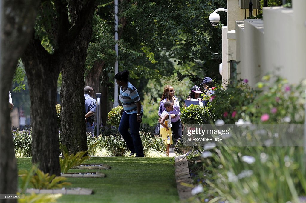 People arrive to vist South Africa's anti-apartheid icon Nelson Mandela at his residence in Johannesburg on December 29, 2012. Nelson Mandela was recovering at his Johannesburg home today, convalescing and receiving further care after a nearly three-week hospital stay, officials said. AFP PHOTO / ALEXANDER JOE