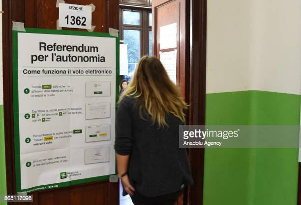 People arrive to vote for the referendum on constitutional reforms offering more autonomy of Region of Lombardia at a polling station in Milan Italy...
