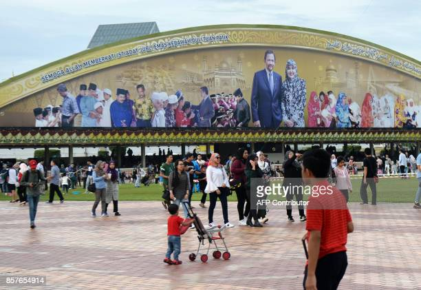 People arrive watch Brunei's Sultan Hassanal Bolkiah ride past on a royal chariot during a procession to mark his golden jubilee of accession to the...