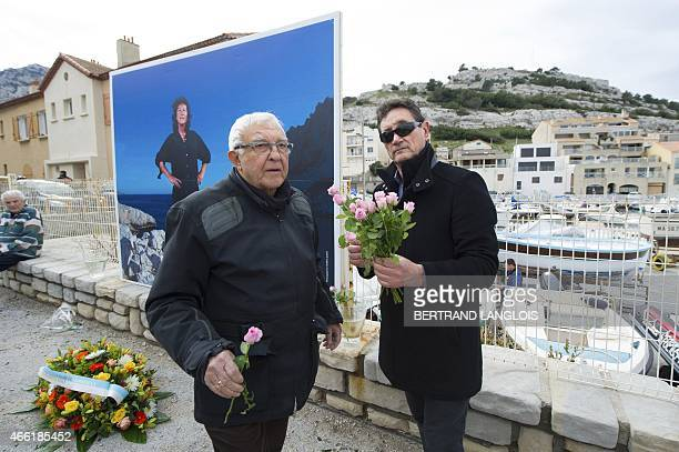 People arrive with floral tributes during a ceremony to pay tribute to late French Champion sailor Florence Arthaud on March 14 2015 in Marseille...