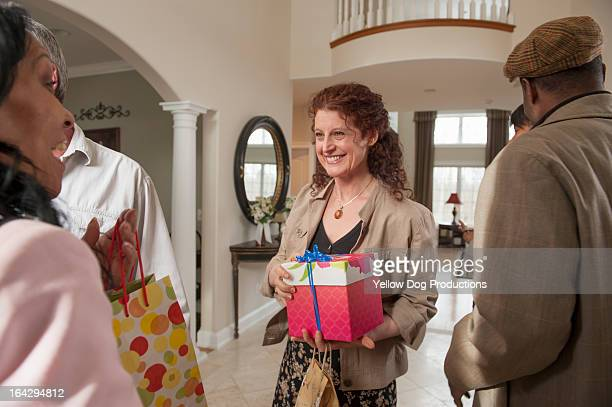 People arriving at house with presents for a party