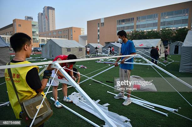 People assemble a tent at a primary school set as the emergency evacuation after the Wednesday explosions of a warehouse in Binhai New Area on August...