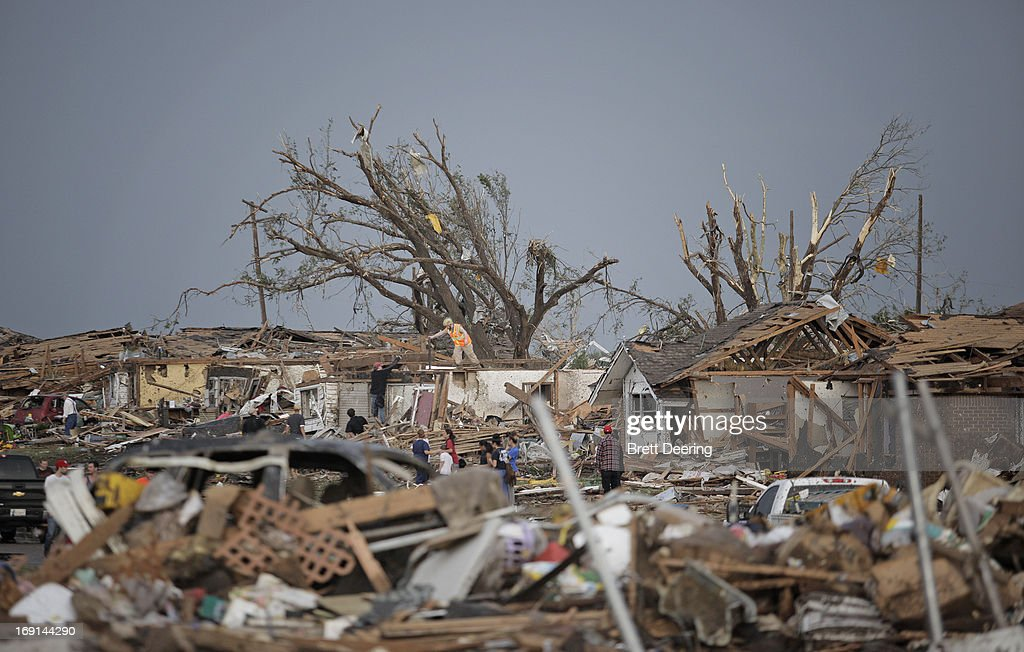 People assess the damage after a powerful tornado ripped through the area on May 20, 2013 in Moore, Oklahoma. The tornado, reported to be at least EF4 strength and two miles wide, touched down in the Oklahoma City area on Monday killing at least 51 people.
