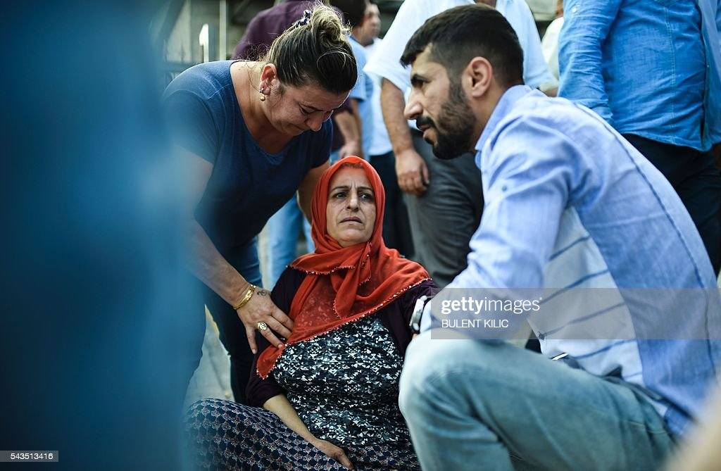 People assist a mother (C) who lost a relative, outside a forensic medicine building close to Istanbul's airport on June 29, 2016, a day after a suicide bombing and gun attack targeted Istanbul's airport, killing at least 36 people. A triple suicide bombing and gun attack that occurred on June 28, 2016 at Istanbul's Ataturk airport has killed at least 36 people, including foreigners, with Turkey's prime minister saying early signs pointed to an assault by the Islamic State group. / AFP / BULENT