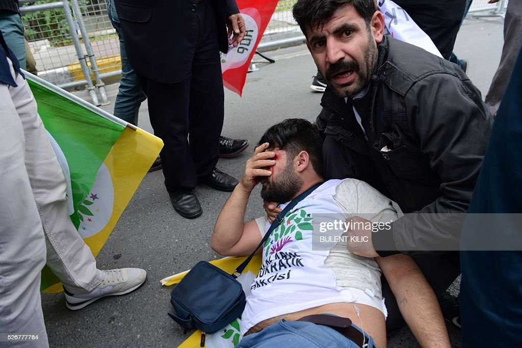 People assist a protestor bleeding from his eye after he was injured during clashes with anti-riot police during a May Day rally in Bakirkoy, a district of Istanbul, on May 1, 2016. Turkish labour activists and leftists marked the annual May Day holiday, with thousands of security deployed and bracing for trouble after the authorities refused to allow protests in central Taksim Square. / AFP / BULENT