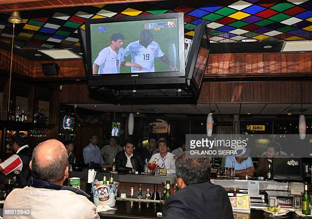 People at a bar in Tegucigalpa on July 8 2009 follow on TV the Concacaf Gold Cup regional football tournament match between Honduras and the United...
