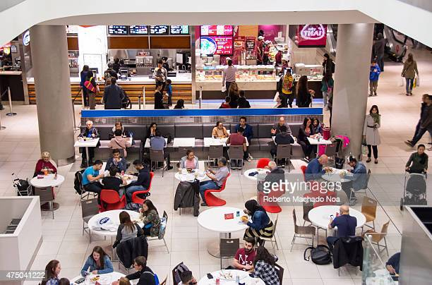People at a food court inside a mall with some people eating at the table and some ordering food from the different restaurants in the area