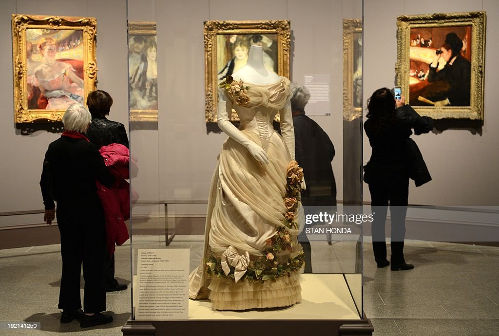 People at a media preview look at an Evening Dress, ca. 1882 by Charles Federick Worth (C, in glass case) and paintings 'Woman with a Pearl Necklace in a Loge, 1879' (L) by Mary Cassatt, 'The Loge, 1874' (C) by Auguste Renoir and 'In the Loge, 1878' (R) by Mary Cassatt in the exhibition 'Impressionism, Fashion, and Modernity' February 19, 2013 at The Metropolitan Museum of Art in New York. The look at the role of fashion in the works of the Impressionists and their contemporaries shows 80 major paintings with period costumes, accessories, fashion plates, photographs, and popular prints. AFP PHOTO/Stan HONDA