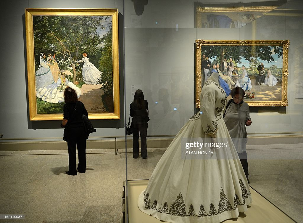 People at a media preview look at 'Day Dress' American 1867 (C, in glass case), 'Women in the Garden, 1866' (L) by Claude Monet and 'Family Reunion, 1867' (R) by Jean-Ferderic Bazille in the exhibition 'Impressionism, Fashion, and Modernity' February 19, 2013 at The Metropolitan Museum of Art in New York. The look at the role of fashion in the works of the Impressionists and their contemporaries shows 80 major paintings with period costumes, accessories, fashion plates, photographs, and popular prints. AFP PHOTO/Stan HONDA