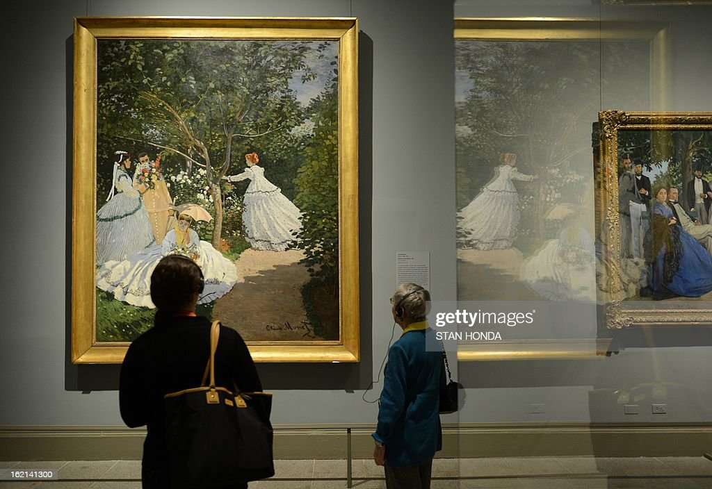 People at a media preview look at 'Women in the Garden, 1866' (L) by Claude Monet in the exhibition 'Impressionism, Fashion, and Modernity' February 19, 2013 at The Metropolitan Museum of Art in New York. The look at the role of fashion in the works of the Impressionists and their contemporaries shows 80 major paintings with period costumes, accessories, fashion plates, photographs, and popular prints. AFP PHOTO/Stan HONDA