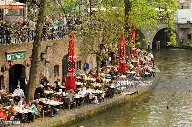People at an outdoor restaurant on the wharf along Oudegracht