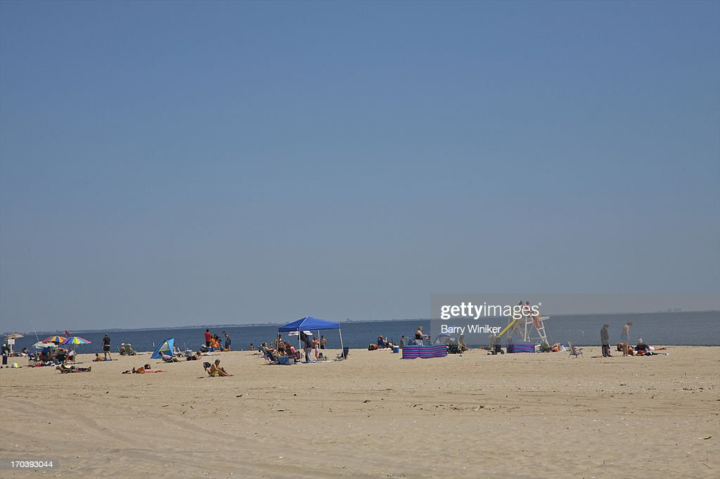 People at beach near water under blue sky