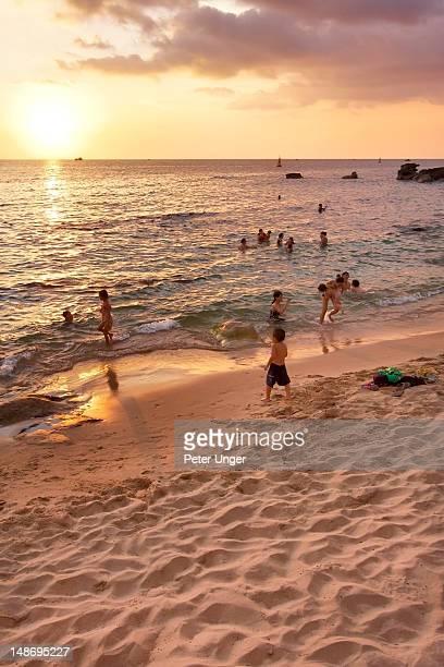 People at Duong Dong beach at dusk.