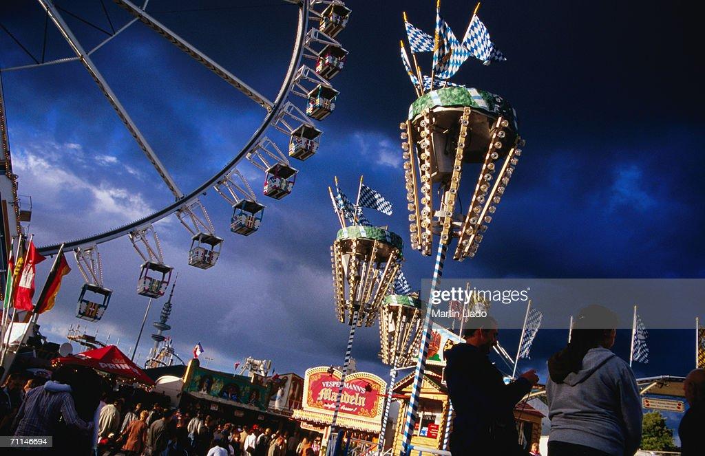 People at Hamburger Dom fun fair with Ferris wheel in background, Hamburg, Germany : Stock Photo