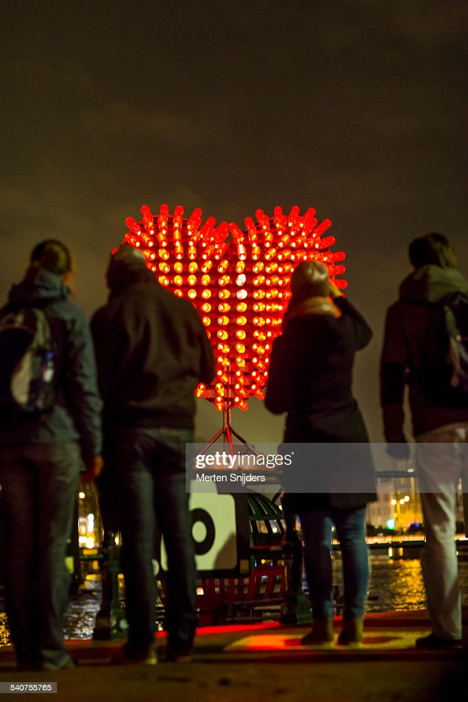 People at heart shaped light installation