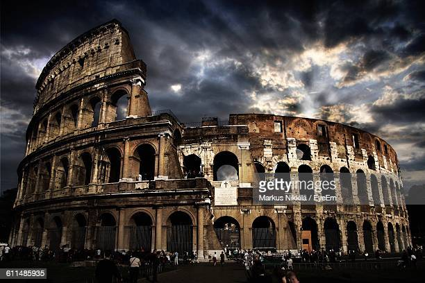 People At Historic Coliseum Against Cloudy Sky