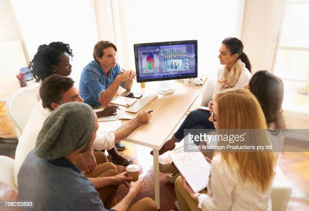 People at meeting with computer in office