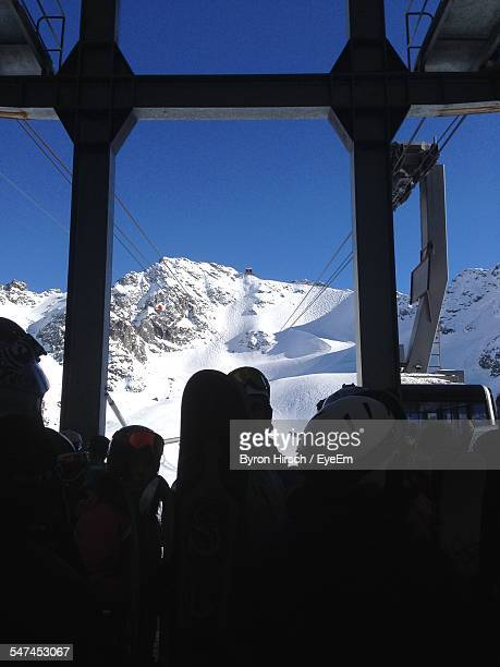 People At Overhead Cable Car Station In Front Of Snowcapped Mountains