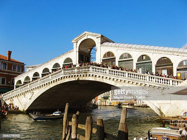People At Rialto Bridge Over Grand Canal Against Clear Blue Sky In City