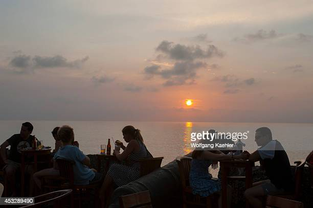 People at sunset in outdoor cafe/restaurant on the city wall of the old walled city of Cartagena Colombia